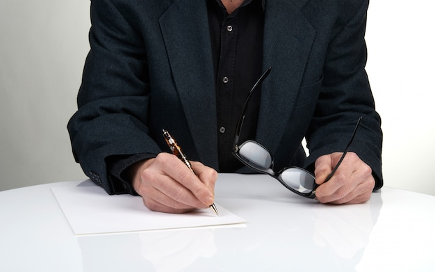 Close up of the hands of a businessman in a suit signing or writing a document on a sheet