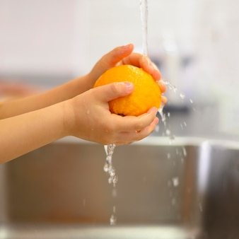 Close-up hands of a child washing a lemon