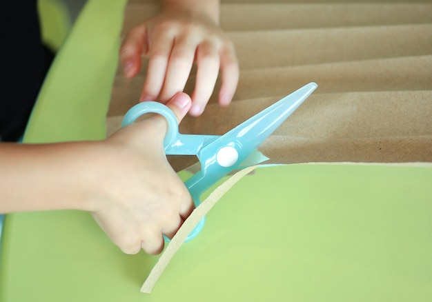 Close up hands of child with plastic scissors cut paper in play room.