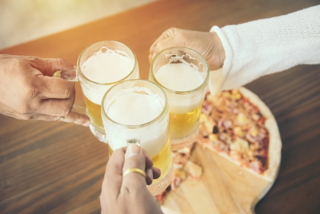 Close up of hands clinking beer mugs and pizza at bar or pub and restaurant