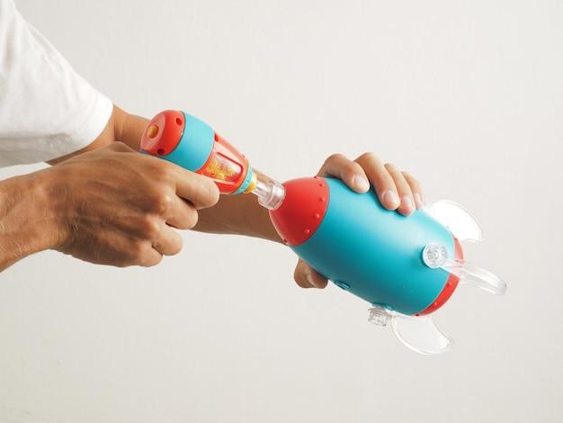 확대. 손은 도구로 장난감 파란색 우주선 로켓을 수집합니다.