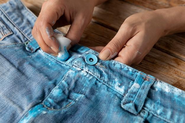 青いペンキでジーンズを着色するクローズアップの手
