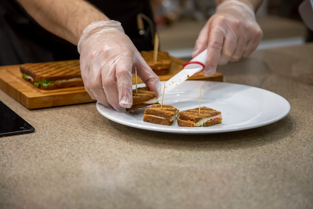 Close up of hands of a cook man in rubber gloves put on a white plate snacks grilled sandwiches. close up, soft focus, background is kitchen in blur