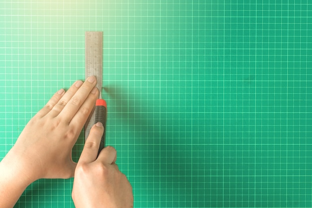 Close up of hands cutting on green board