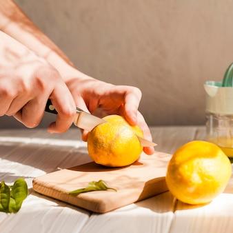 Mani del primo piano che tagliano limone