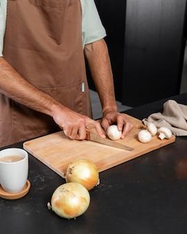 버섯을 절단하는 손을 닫습니다