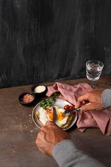Крупным планом руки режут бутерброд