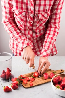 Close-up hands cutting strawberries