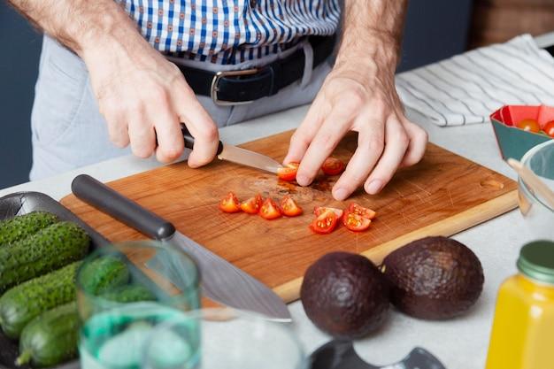 Mani ravvicinate che tagliano i pomodori