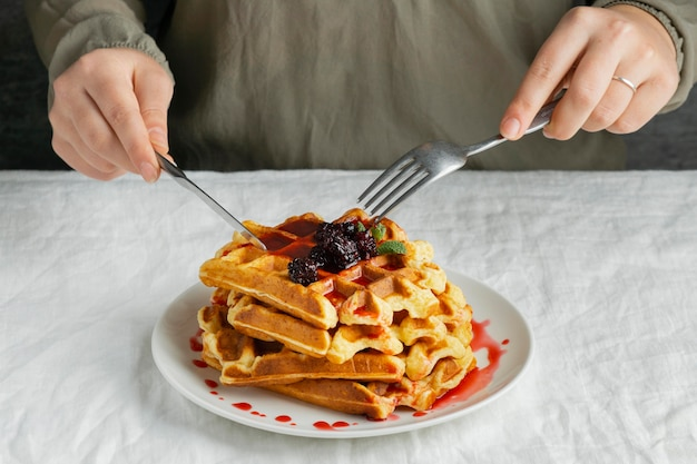 Close-up hands cutting waffles