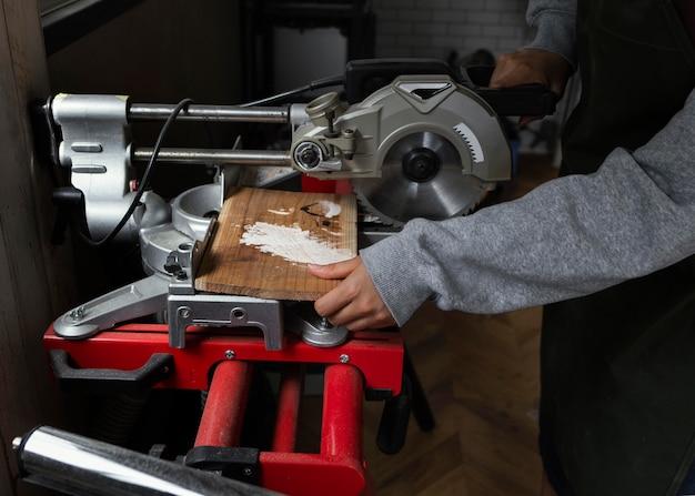 Chiuda sulle mani che tagliano il legno