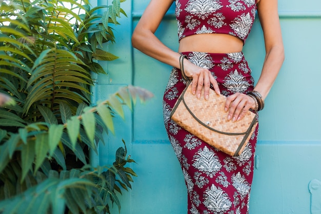 わらのハンドバッグ、青い壁にポーズをとってスタイリッシュな美しい女性、印刷された衣装、夏のスタイル、ファッショントレンド、トップ、スカート、スキニー、アクセサリー、熱帯の休暇を保持している手の詳細を閉じる