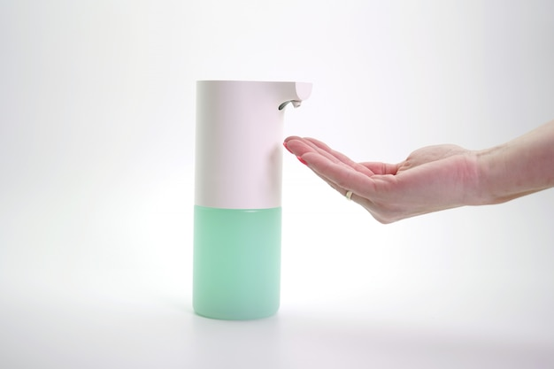 Close-up of hands disinfected with a foam automatic dispenser, isolated wall. protection from viruses and bacteria