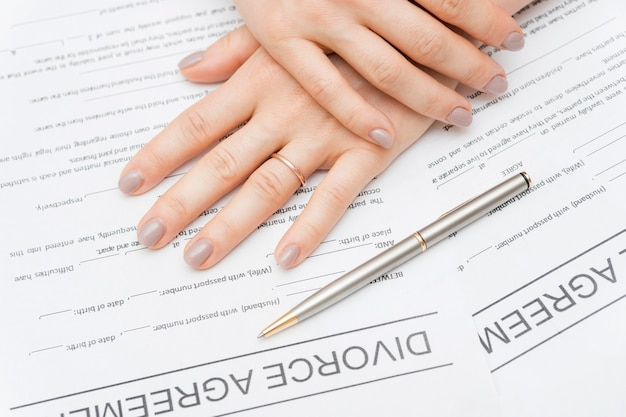 Close-up hands on divorce agreement