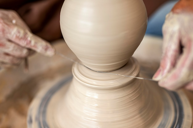 Крупным планом руки делают керамику с нитью