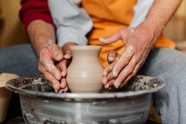 Chiudere le mani facendo ceramiche