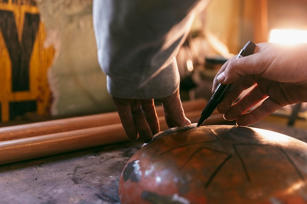 Mani del primo piano che disegnano sull'oggetto del metallo