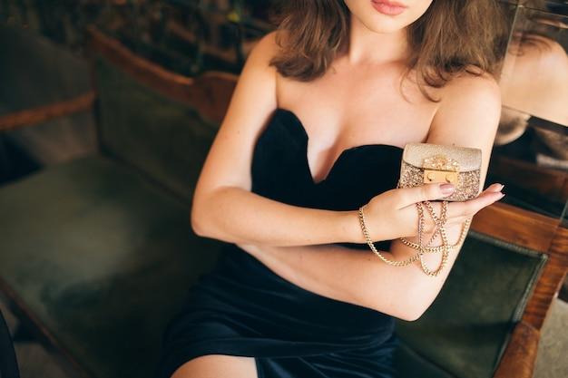 Chiudere le mani di elegante bella donna seduta nel caffè vintage in abito di velluto nero che tiene piccola borsa d'oro in mano, ricca signora elegante, accessori alla moda moda elegante