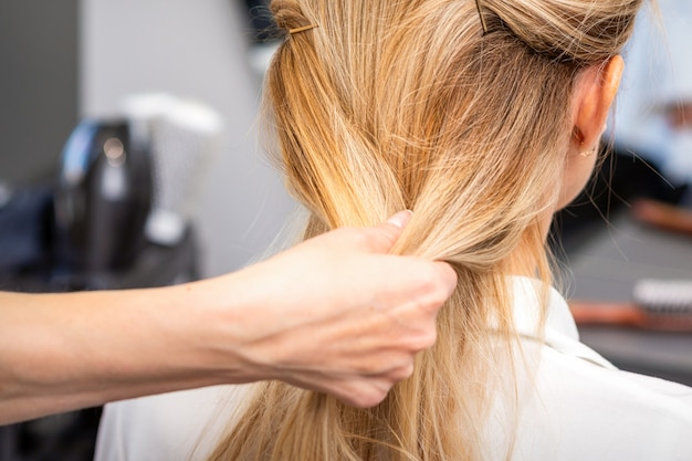 Close up of hands of female hairdresser styling hair of a blonde woman in a hair salon