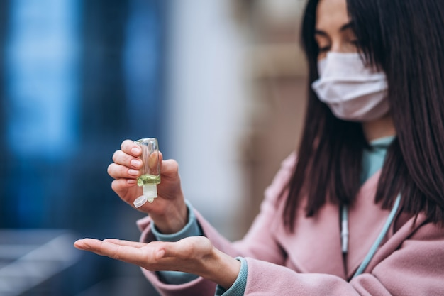 Close up hands of female in medical mask cleaning her hands with sanitizer outdoor in the city to prevent virus deseases. coronavirus, covid-19, epidemic, pandemic, quarantine concept.