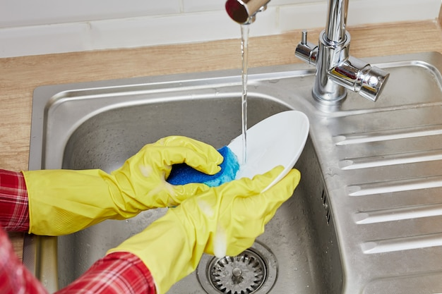 Close up hands in gloves of woman washing dishes in kitchen with sponge