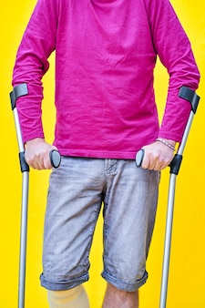 Close-up of the hands gripping crutches of a man in jeans and purple t-shirt with a bandaged leg.