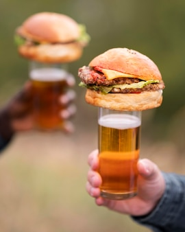 Close-up hands holding beer and burgers