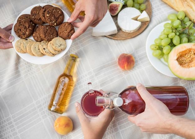 Mani del primo piano che tengono bottiglia e piatto