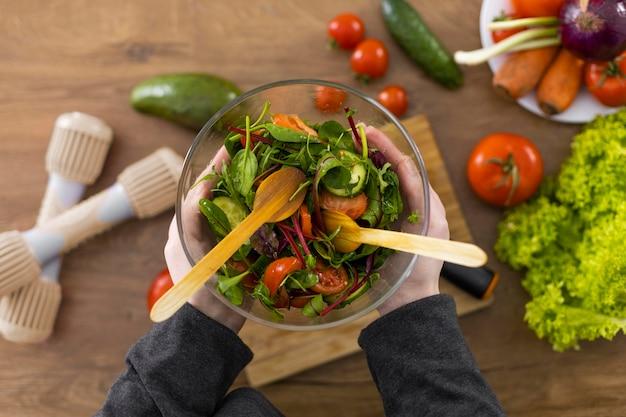 Chiuda sulle mani che tengono la ciotola con insalata