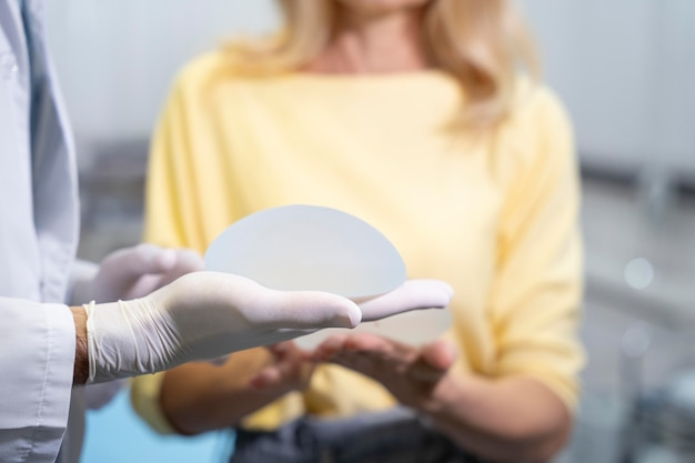 Close up hands holding breast implant