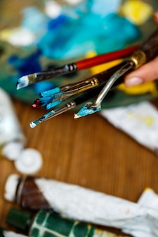 Close up of hands holding brushes and palette knife