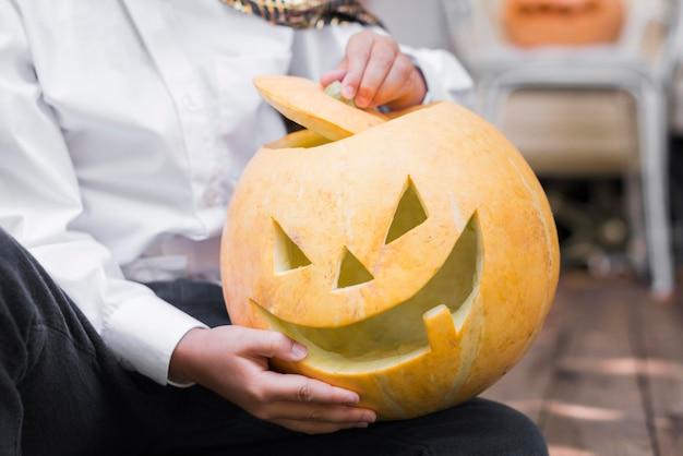 Close-up hands holding carved pumpkin