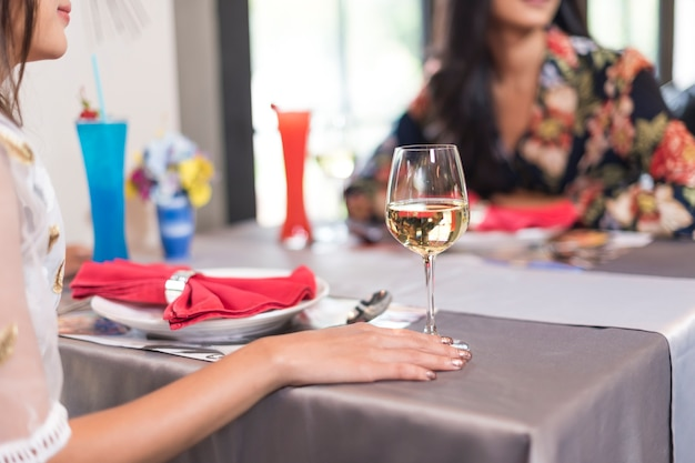 Close-up of hands holding champagne flutes during celebration on dining table