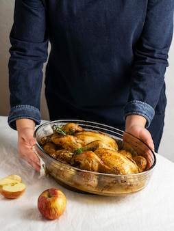 Close-up hands holding chicken and potatoes dish