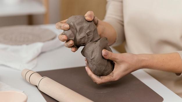 屋内で粘土を保持しているクローズアップの手