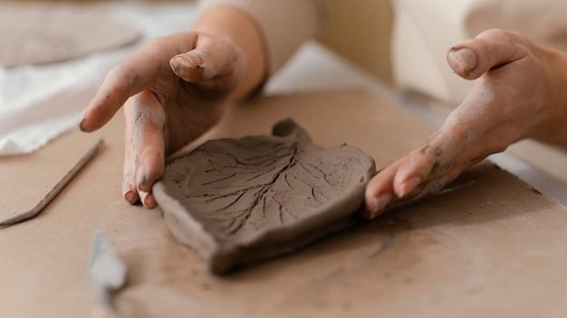 Mani del primo piano che tengono foglia dell'argilla
