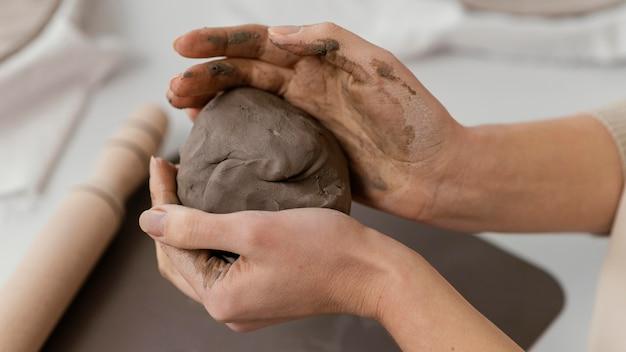 粘土を保持しているクローズアップの手
