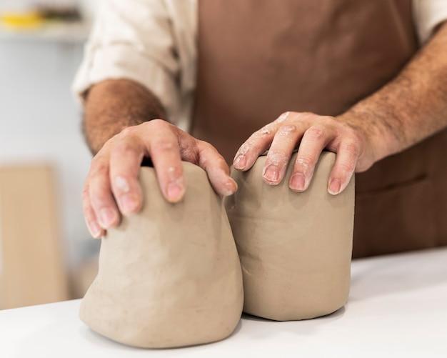 Закройте руки, держащие глину