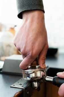 コーヒー作りのアイテムを持って手を閉じる
