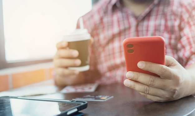 Close-up hands holding coffee paper cup and smartphone while sitting at coffee shop. businessman drinking coffee and smiling. freelancer working and checking email and chatting with customer. trader