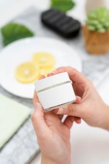 Mani del primo piano che tengono il contenitore della crema