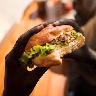 Close-up hands holding delicious burger