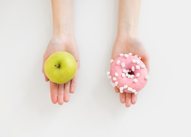 Close up hands holding doughnut and apple