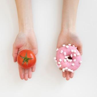 Mani ravvicinate che tengono ciambella e pomodoro