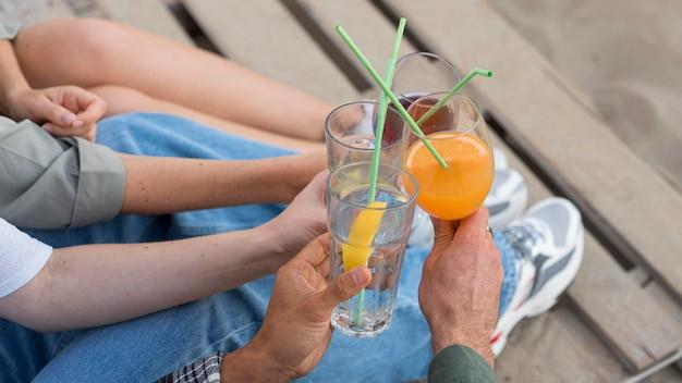 Mani del primo piano che tengono le bevande