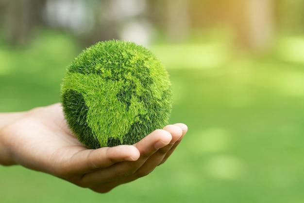 녹색 배경에 지구를 들고 손을 닫습니다 자연 보호 지구를 보호