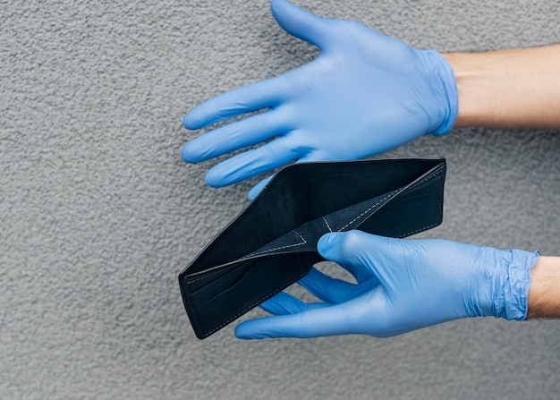 Mani del primo piano che tengono portafoglio vuoto