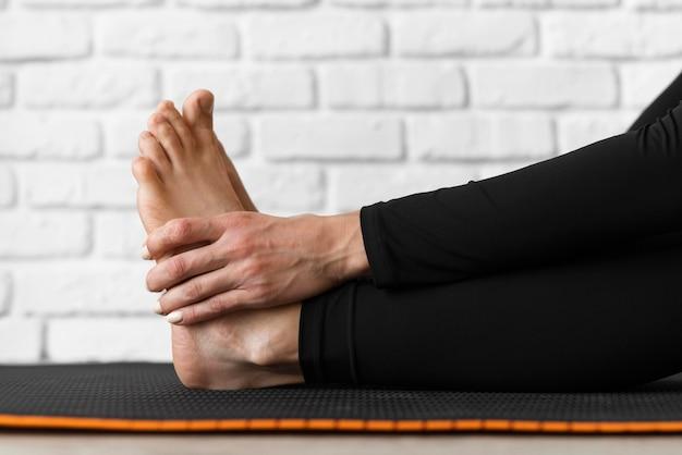 Mani del primo piano che tengono i piedi