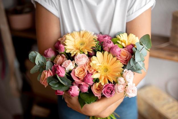 Крупным планом руки, держа букет цветов
