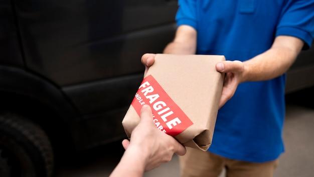 Mani ravvicinate che tengono un pacco fragile